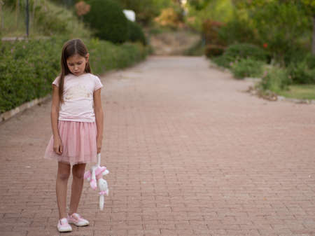 Sad girl hugging teddy bear sadness alone in green garden park. Lonely girl feeling sad unhappy walking outdoors with best friend toy. Autism child play teddy bear best friend. Family violence concept 版權商用圖片