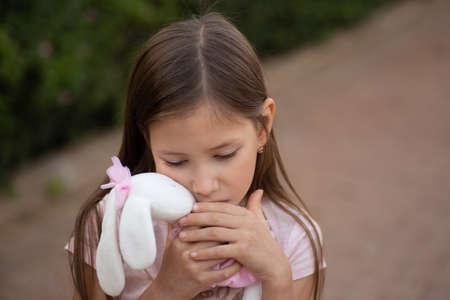 Sad upset Caucasian girl hugging toy. Child embrace soft plush bear in park outdoors. Lost lonely child kid outside. Unhappy childhood problems lifestyle. 版權商用圖片