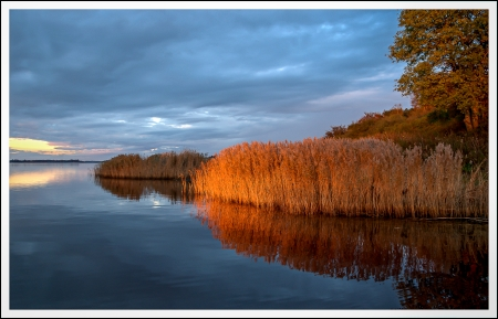 Autumn reflections along in water at sunset