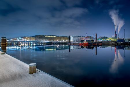 Waterfront of harbor with bridge and smoky chimneys i winter night