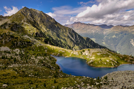 val: A mountain lake in Val di Sole seen from above in a spell of sun