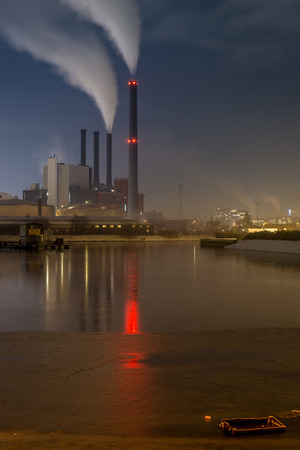 Power plant on water front by night with smoke in the chimneys Editorial