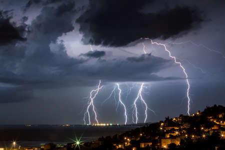 thunder: Massive cloud to ground lightning bolts hitting the horizon of city lights