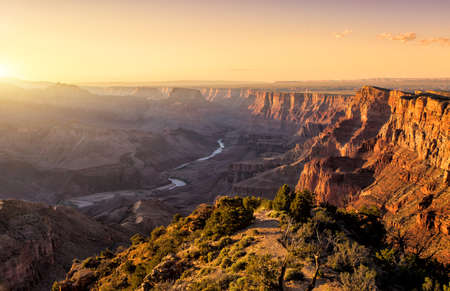 landscape background: Sunset in the Grand Canyon is a steep-sided canyon carved by the Colorado River in the state of Arizona in the United States.