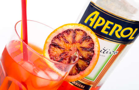 TRIESTE, ITALY, March, 9, 2016; Glass of light drink and ice cube with bottle of Aperol, Aperitivo Poco Alcolico, Liqueur alc.11%. Famous Italian aperitif. Produced by Fratelli Barbieri S.P.A., Italy