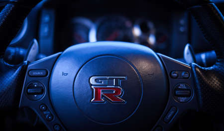 SISTIANA, ITALY JUNE 12, 2013: Photo of  Logo Nissan GT-R Black Edition. The Nissan GT-R is a 2-door 2+2 sports car produced by Nissan and unveiled in 2007. BLUE TONING.