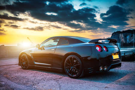 r: SISTIANA, ITALY JUNE 12, 2013: Photo of a Nissan GT-R Black Edition. The Nissan GT-R is a 2-door 2+2 sports car produced by Nissan and unveiled in 2007.