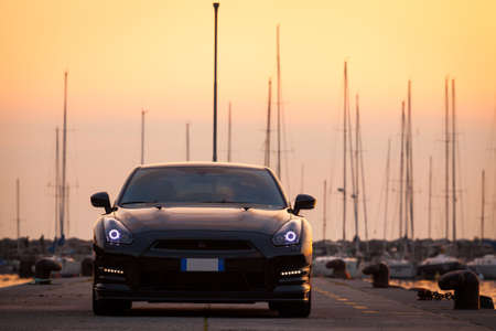 gt: SISTIANA, ITALY JUNE 12, 2013: Photo of a Nissan GT-R Black Edition. The Nissan GT-R is a 2-door 2+2 sports car produced by Nissan and unveiled in 2007.