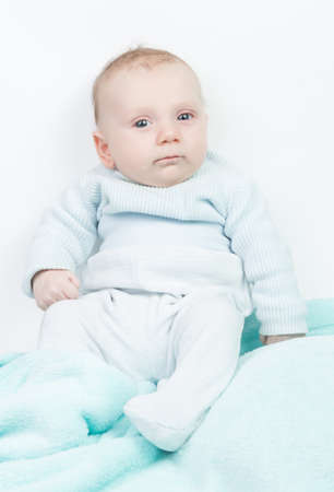 0 3 months: Happy child with blue eyes and turquoise romper Stock Photo