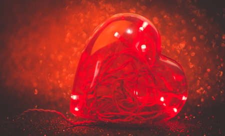 plastic heart: Led lights inside plastic heart with defocused red glitter background. TONED Image. Stock Photo