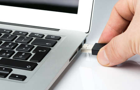 Inserting Usb key or cable into a laptop computer Stock Photo