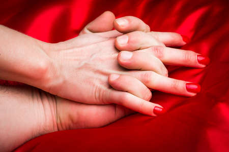 adult nude: Young couple holding hands sensually on red silk bed.