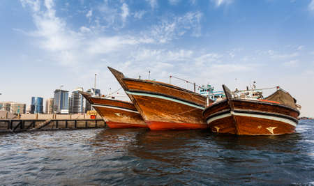 gcc: DUBAI, UAE-MAY17 2015: Dhows old wooden sailing vessels are docked along the Deira side of Dubai Creek