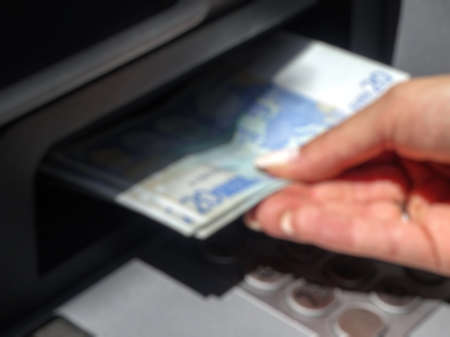 bank withdrawal: Abstract blurry background : hand withdrawing money from outdoor bank ATM