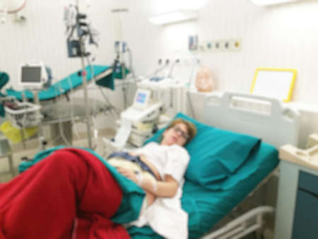 contractions: Blurred image of pregnant patient in hospital bed for background usage.