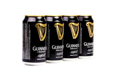 cerveza negra: Trieste, italiano julio 08 2016: Cuatro Guinness stout lata de aluminio en el fondo blanco. dry stout irlandesa se originó en la fábrica de cerveza de Arthur Guinness, Dublín. Una de las marcas de cerveza de mayor éxito en todo el mundo.