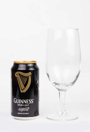 cerveza negra: Trieste, italiano julio 08 2016: Guinness stout lata de aluminio y vidrio de cerveza en el fondo blanco. dry stout irlandesa se origin� en la f�brica de cerveza de Arthur Guinness, Dubl�n. Una de las marcas de cerveza de mayor �xito en todo el mundo.