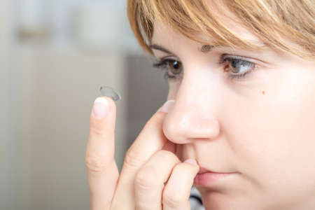 shortsighted: Young womangirl putting contact lens in her eye close up with copy space . Selective Focus. Stock Photo