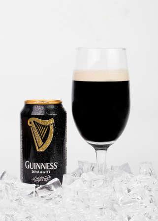 stout: Trieste, italiano julio 08 2016: Guinness stout lata de aluminio y vidrio de cerveza en el fondo blanco. dry stout irlandesa se originó en la fábrica de cerveza de Arthur Guinness, Dublín. Una de las marcas de cerveza de mayor éxito en todo el mundo.
