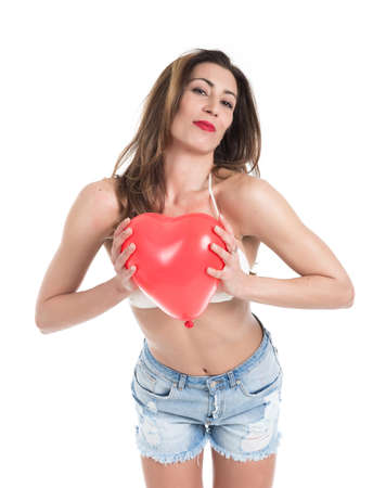 Beautiful young brunette woman in white bikini  playing with red heart shape balloon isolated on white background