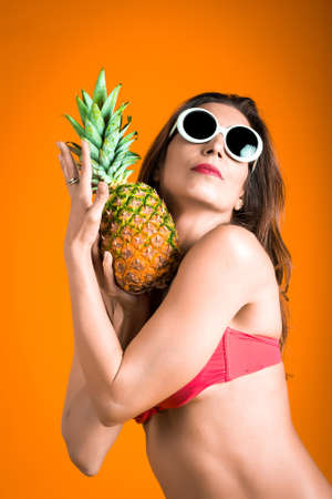 Portrait of young healthy beautiful woman in red bikini and white sunglasses with fresh pineapple in a hand. Funny Fruit Concept. Isolated on orange background with vignette