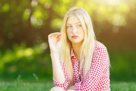 Beautiful young blonde woman with denim shorts and checked shirt relaxing in the park