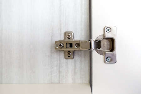 Adjustable concealed hinge fixed on a cabinet Stock Photo