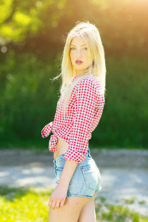 Beautiful young blonde woman with denim shorts and checked shirt enyoing in the park
