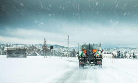 Servizio invernale camion o spargisale spargendo sale sulla superficie stradale per evitare la formazione di ghiaccio nella giornata invernale di neve tempestosa.