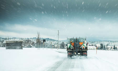 Winter service truck or gritter spreading salt on the road surface to prevent icing in stormy snow winter day.  Stock Photo