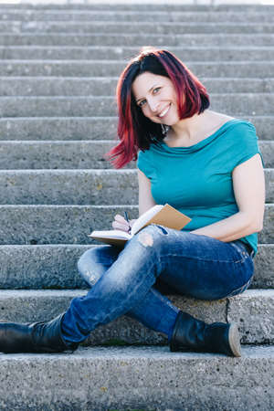 Handsome redhead young woman sitting on the stone stairs and  reading a book. - Concept Relaxing in nature.