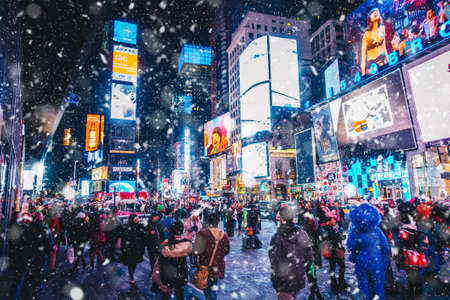 New York City, USA - March 18, 2017: People and famous led advertising panels in Times Square during the snow, one of the symbol of New York City. 新闻类图片
