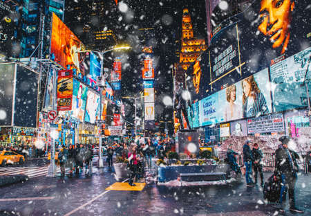 New York City, USA - March 18, 2017: People and famous led advertising panels in Times Square during the snow, one of the symbol of New York City.