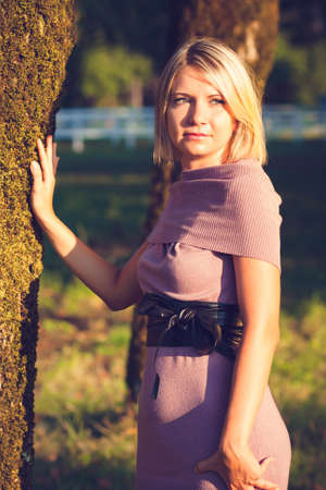 Portrait of fashionable young sensual blonde woman in garden enyoing on the grass field at sunset.