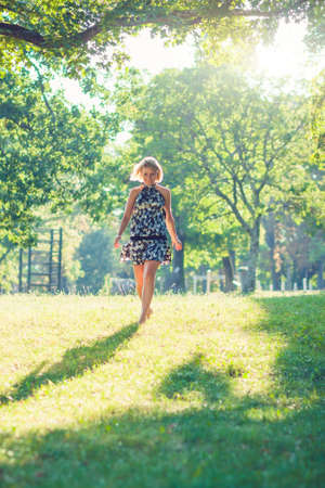 Portrait of fashionable young sensual blonde woman in garden enyoing on the grass field.