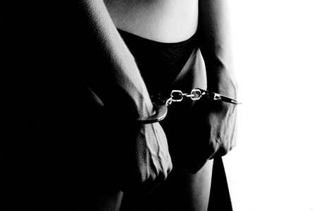 Young woman in black underwear with handcuffs. Concept Fetish Bondage.