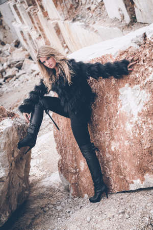 Fashionable young woman posing in, rocky background, quarry Stock Photo