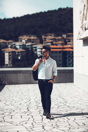 Portrait of a successful young businessman dressed leaning to wall . Concept Fashionable Young Man