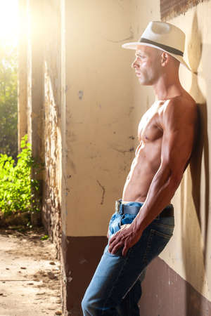 Beautiful male with blue eyes and sexy muscular body wear denim jeans and white hat with torso. Fitness male with healthy tan posing.