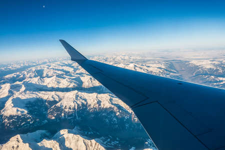 Looking through the window aircraft during flight a snow covered Italian and Osterreich Alps with blue sky without clouds. 스톡 콘텐츠 - 144320471
