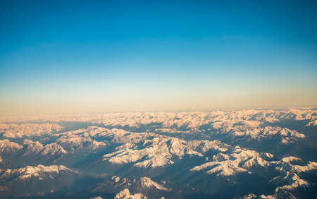 Looking through the window aircraft during flight a snow covered Italian and Osterreich Alps with blue sky without clouds. 스톡 콘텐츠 - 144320495