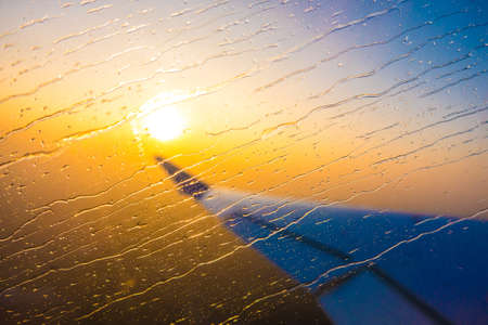 Looking through the window aircraft during flight a beautiful sunrise. 스톡 콘텐츠