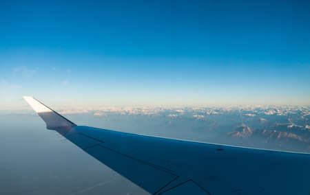 Looking through the window aircraft during flight a snow covered Italian and Osterreich Alps with blue sky without clouds. 스톡 콘텐츠 - 144320550