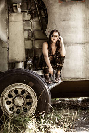 Portrait of a young girl with mimetic military dress near the old abandoned broken plane. Concept military strong woman. 스톡 콘텐츠
