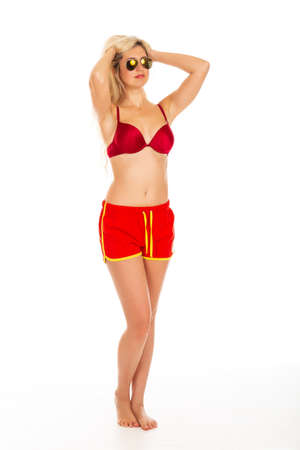 Pretty young blonde woman posing with basketball, dressed in red shorts and red bikini. Concept Woman in bikini.