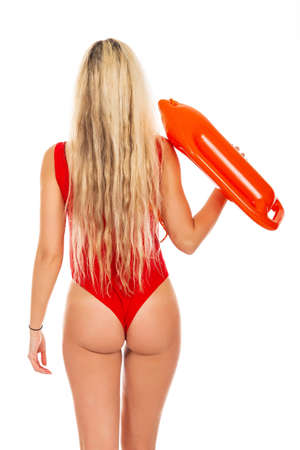Pretty young blonde lifeguard in red sexy swimsuit with lifeguard rescue can floating buoy tube on the white background. Concept Woman in Swimsuite. 스톡 콘텐츠 - 145158926