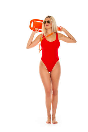 Pretty young blonde lifeguard in red sexy swimsuit with lifeguard rescue can floating buoy tube on the white background. Concept Woman in Swimsuite.