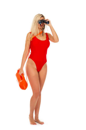 Pretty young blonde lifeguard in redswimsuit with lifeguard rescue can floating buoy tube and  binocular on the white background. Concept Woman in Swimsuite.  스톡 콘텐츠