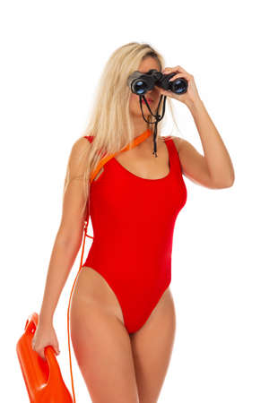 Pretty young blonde lifeguard in redswimsuit with lifeguard rescue can floating buoy tube and  binocular on the white background. Concept Woman in Swimsuite. 스톡 콘텐츠 - 145111534