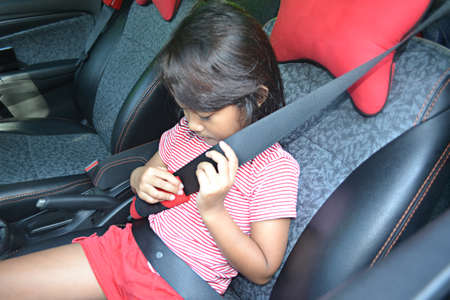 Asian Little Girl Holding The Seat Belt And Feel Comfortable After Wearing A Seat Belt Before Traveling